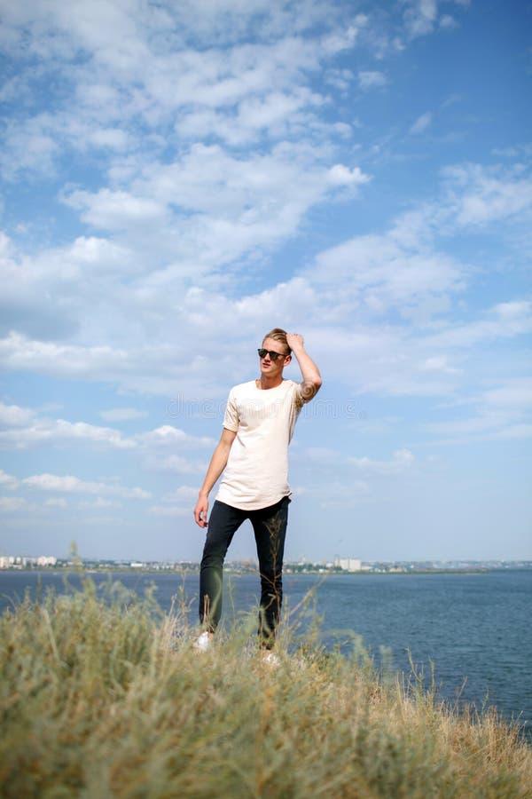 Giovane sicuro in occhiali da sole su uno sfondo naturale Un tipo che sta vicino al fiume Concetto di viaggio Copi lo spazio immagine stock