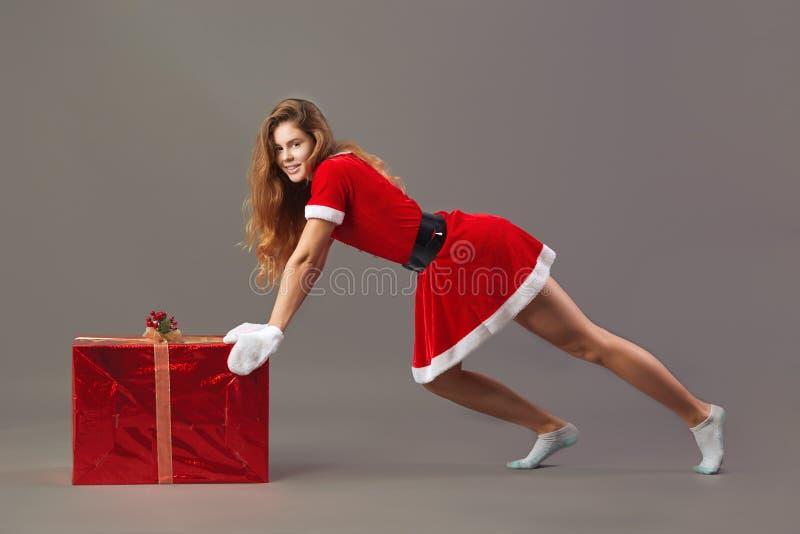 Giovane sig.ra piacevole Santa Claus ha vestito in rosso l'abito, guanti bianchi ed i calzini bianchi spinge il regalo di Natale  fotografia stock