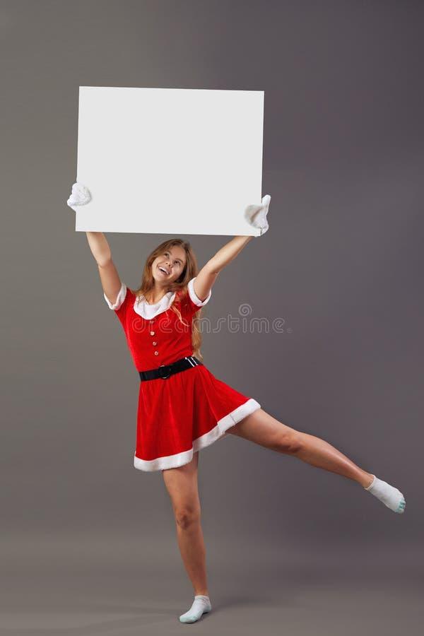Giovane sig.ra piacevole Santa Claus ha vestito in rosso l'abito, guanti bianchi ed i calzini bianchi tiene la tela bianca sopra  fotografia stock libera da diritti