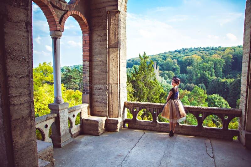 Giovane signora affascinante in vestito d'annata sul balcone del castello immagini stock libere da diritti