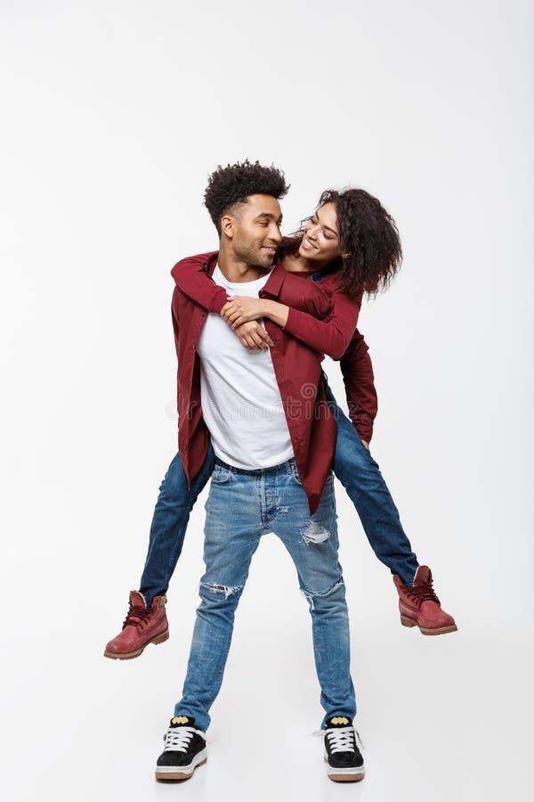 Giovane signora afroamericana attraente integrale che guida indietro sulla sua parte posteriore del ragazzo e gode di di giocare  fotografia stock libera da diritti