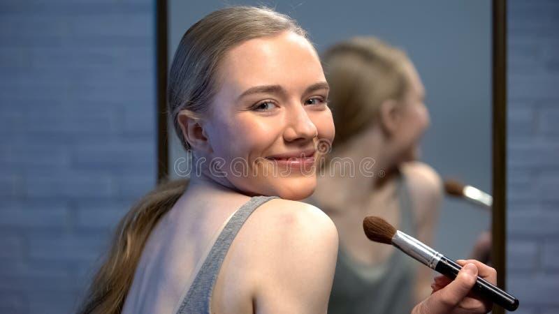 Giovane signora alla moda graziosa che applica la parte anteriore della cipria dello specchio che sorride sulla macchina fotograf fotografie stock