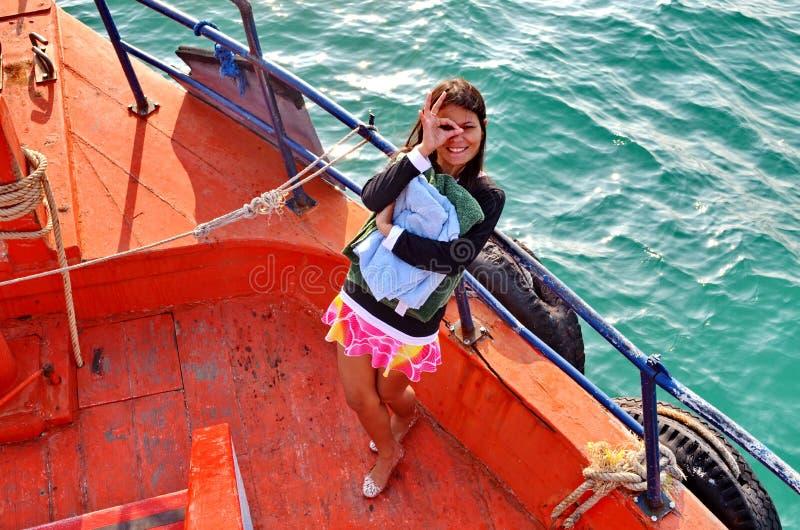 Giovane signora asiatica dà una strizzatina d'occhio mentre sta alla prua di una barca fotografia stock
