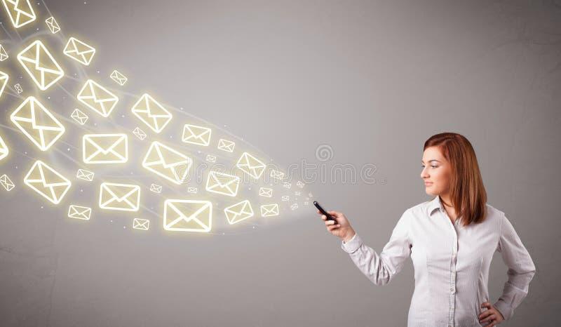 Giovane signora attraente che tiene un telefono con le icone del messaggio immagini stock