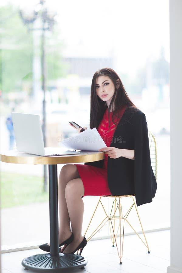 Giovane signora bella in vestito d'avanguardia con i documenti e telefono al computer portatile della tavola immagine stock libera da diritti