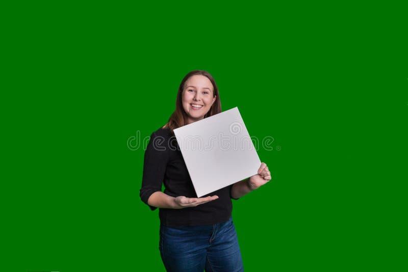 Giovane signora bionda che presenta un bordo bianco in bianco davanti alla sua espressione felice fotografie stock