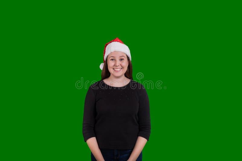 Giovane signora bionda graziosa che indossa sorridere del cappello di Santa Claus fotografia stock