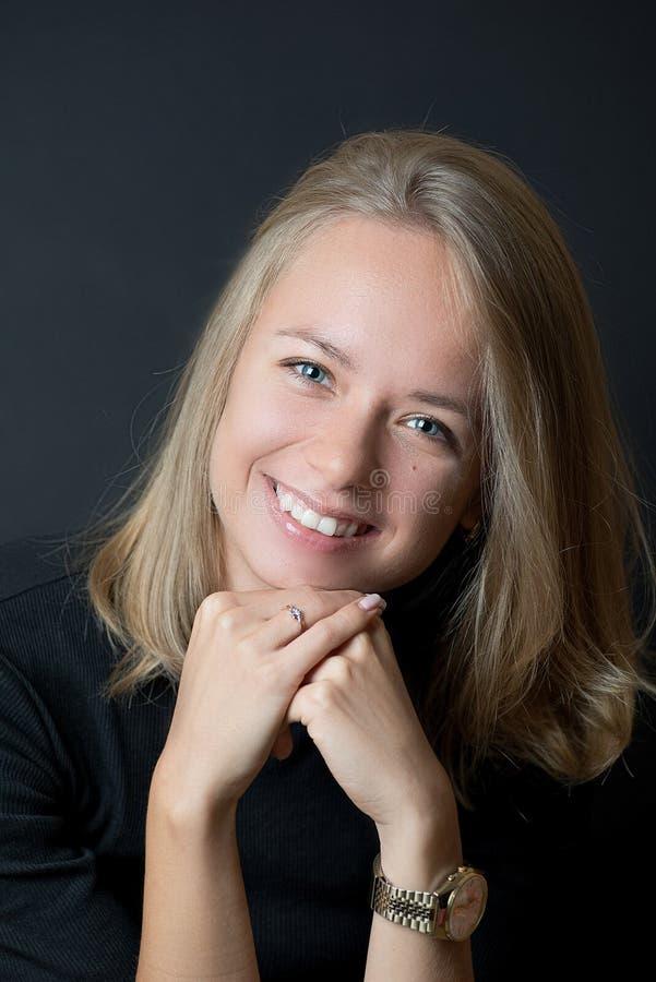 Giovane signora bionda in maglietta nera che sorride con i denti immagini stock libere da diritti