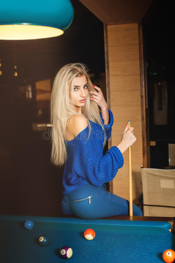Giovane signora bionda sensuale che posa sul biliardo con l'indicazione immagine stock