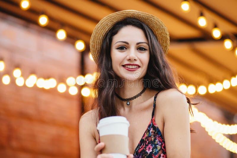 Giovane signora castana in cappello e vestito di paglia di estate, avendo trucco, tenente tazza di carta con la bevanda calda, av immagine stock