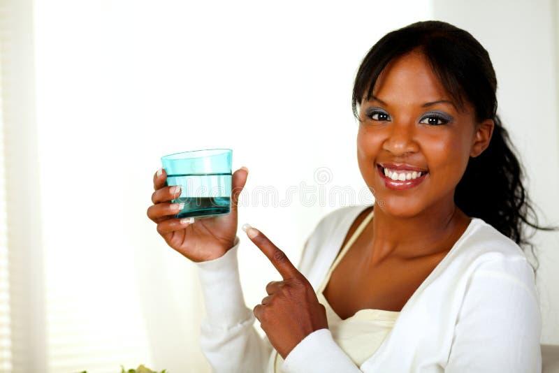 Giovane signora che indica un vetro dell'acqua dolce fotografie stock