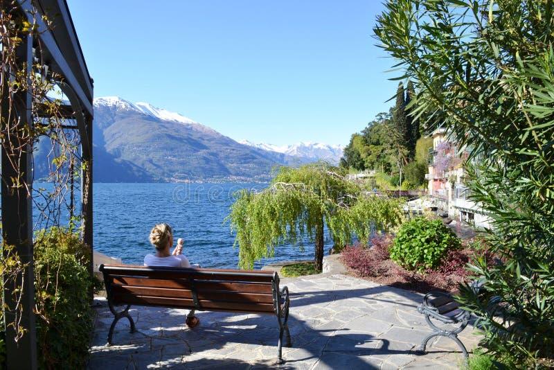 Giovane signora che mangia un gelato che si siede su un banco al fronte lago di Como del lago in un bello giorno di molla soleggi fotografia stock