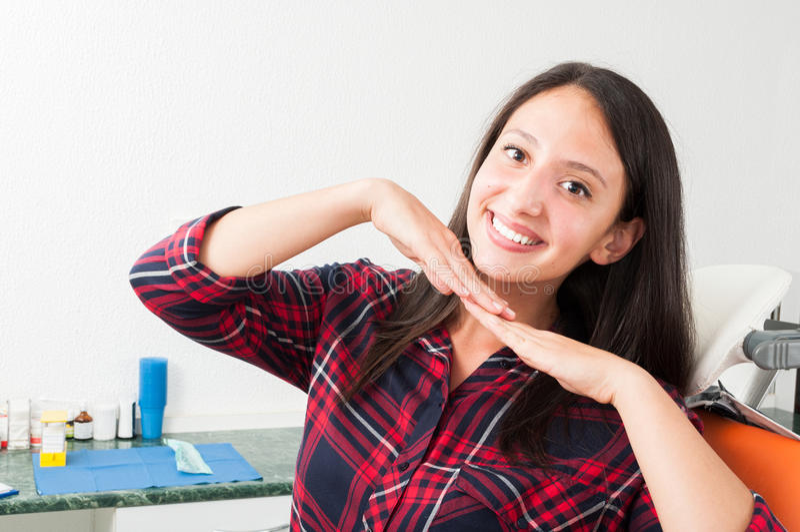 Giovane signora che posa con il sorriso perfetto nella sedia del dentista fotografia stock libera da diritti