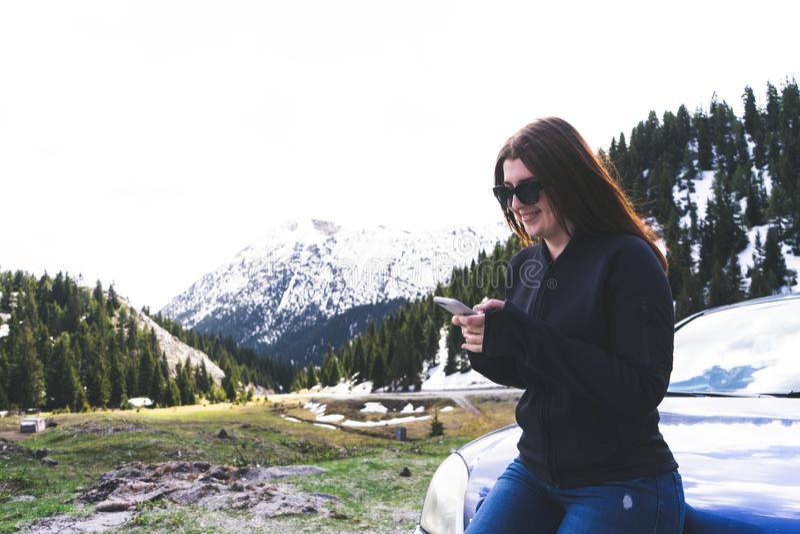 giovane signora che si siede su un cofano di un'automobile facendo uso dello Smart Phone nelle montagne Ragazza felice che invia  fotografia stock libera da diritti
