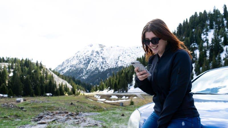 giovane signora che si siede su un cofano di un'automobile facendo uso dello Smart Phone nelle montagne Ragazza felice che invia  immagini stock libere da diritti