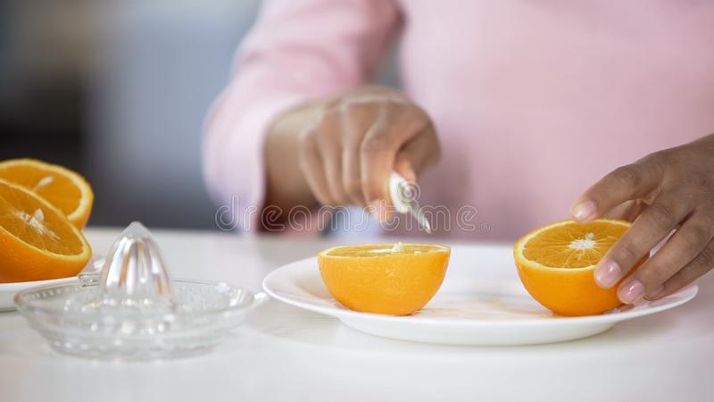 Giovane signora che taglia arancia con il coltello sul piatto, cucinante succo fresco nella mattina immagine stock
