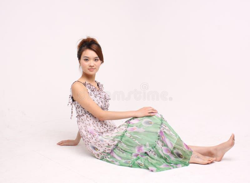 Giovane signora cinese in abbigliamento casuale che si siede sul pavimento fotografia stock