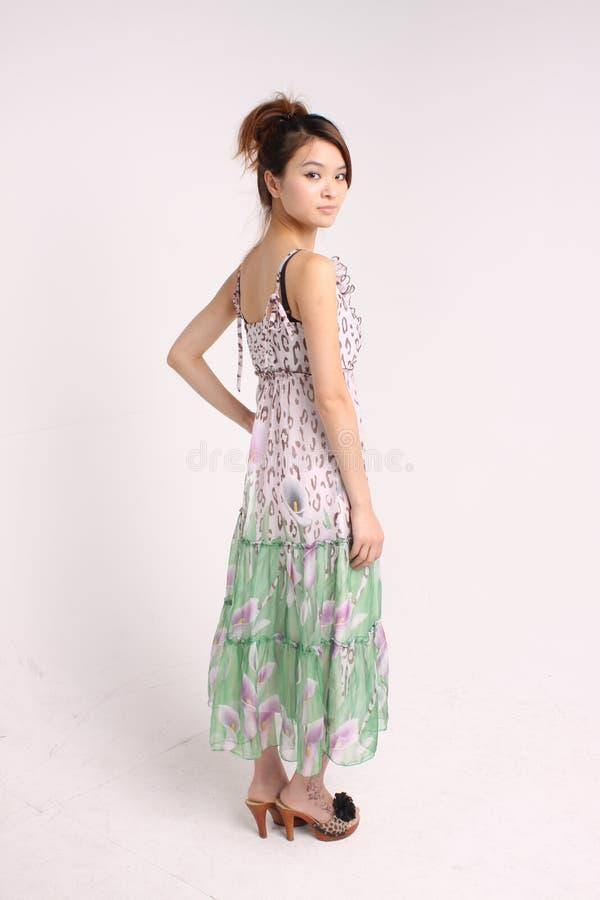 Giovane signora cinese in abbigliamento casuale che sta e che guarda lateralmente fotografie stock libere da diritti
