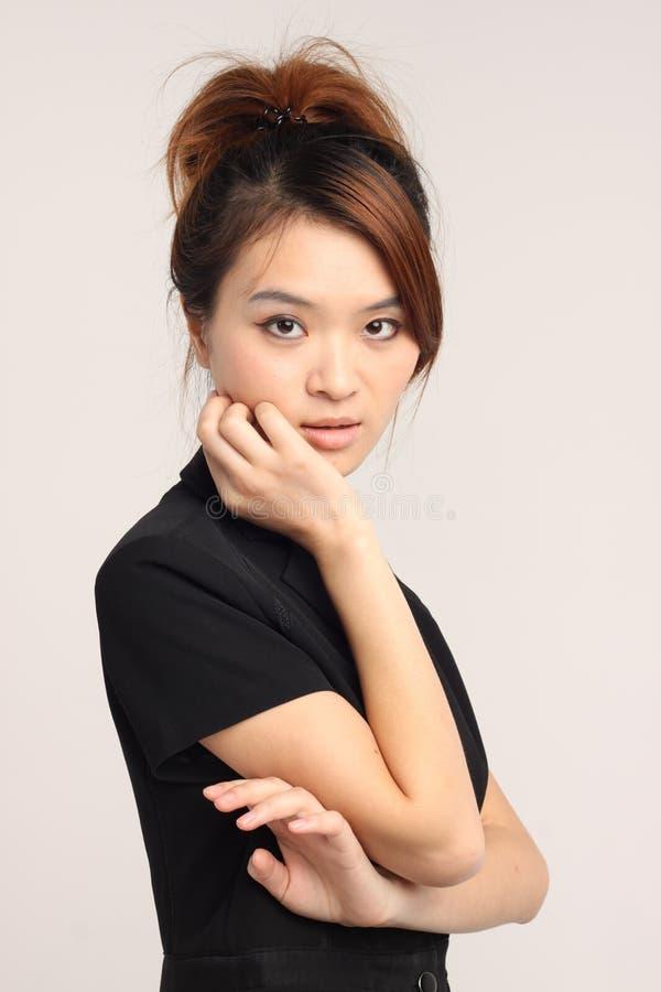 Giovane signora cinese in abbigliamento convenzionale con lo sguardo ansioso e confuso fotografie stock