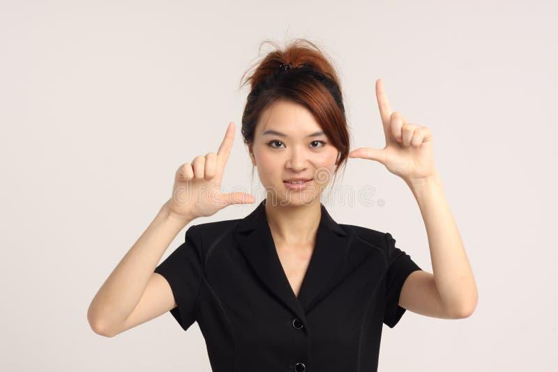 Giovane signora cinese nella posa convenzionale di macchina-clic dell'abbigliamento fotografia stock libera da diritti