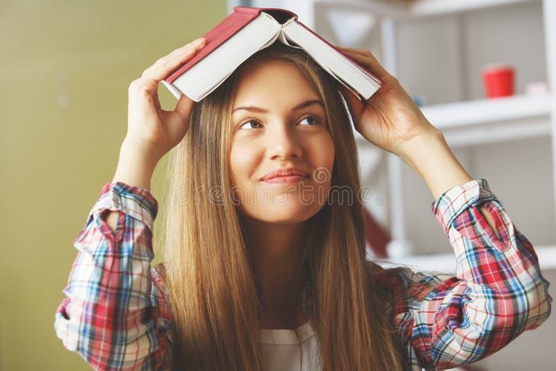 Giovane signora con il libro sopraelevato fotografie stock libere da diritti