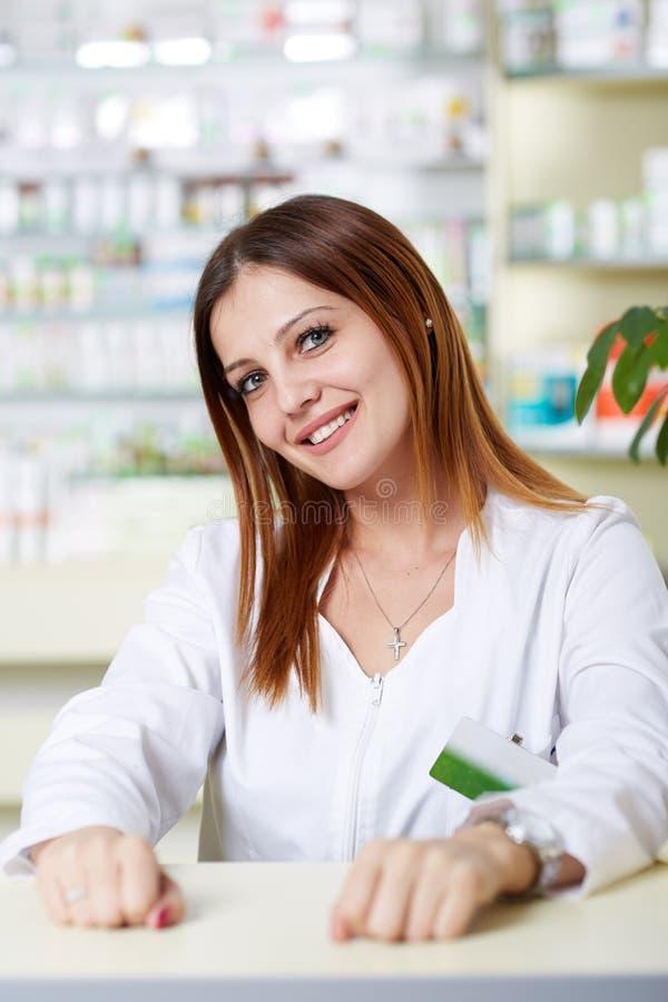 Giovane signora del farmacista allo scrittorio fotografia stock libera da diritti