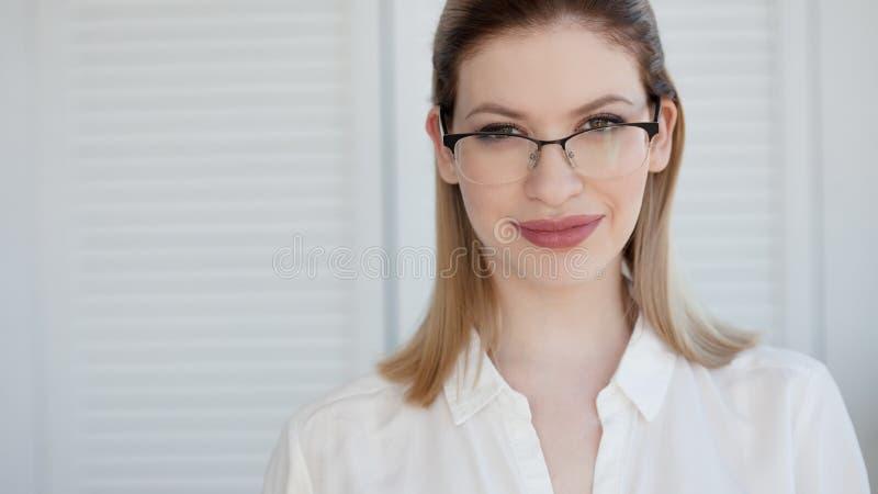 Giovane signora di affari in camicia e vetri bianchi Sorridere attraente della giovane donna immagine stock libera da diritti