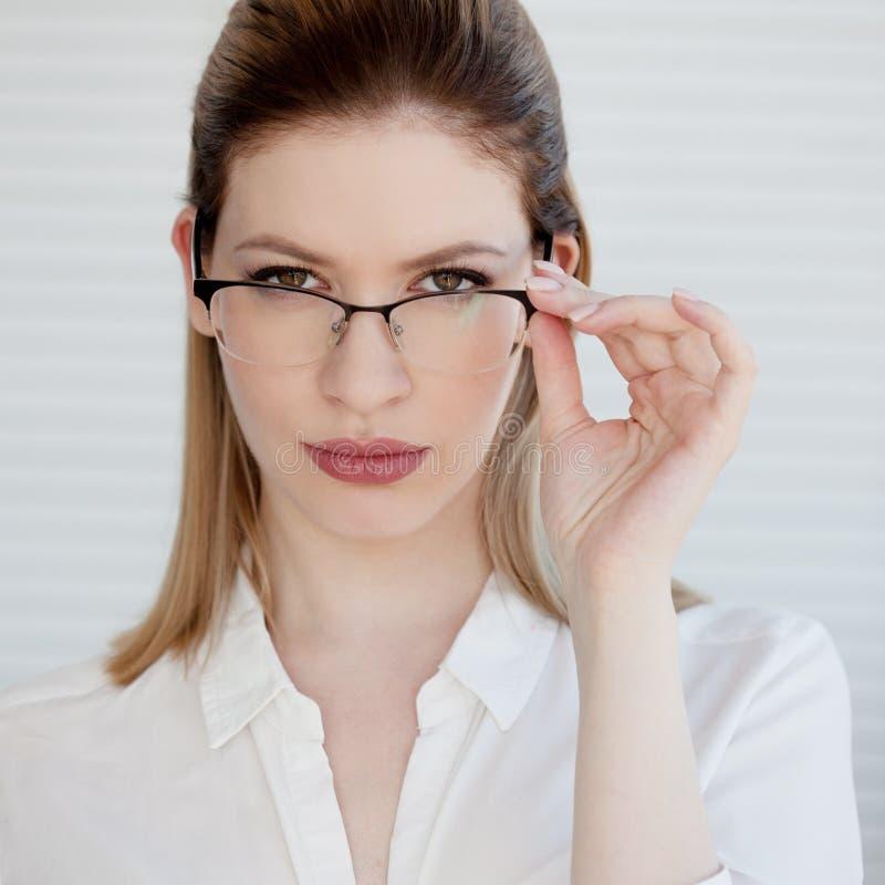 Giovane signora di affari in camicia e vetri bianchi Sorridere attraente della giovane donna fotografia stock libera da diritti