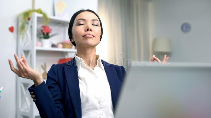 Giovane signora di affari che medita computer portatile anteriore che riduce sforzo, tecnica di rilassamento immagine stock libera da diritti