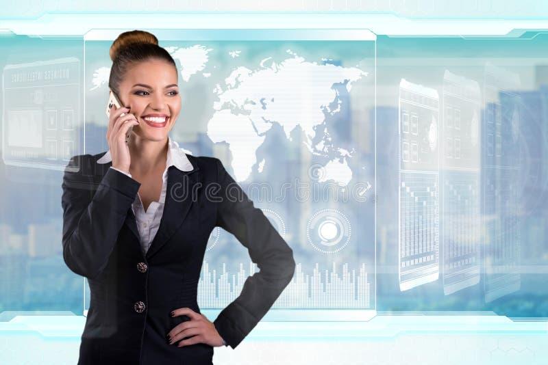 Giovane signora di affari parla sul telefono e sugli impianti in ufficio futuristico fotografie stock