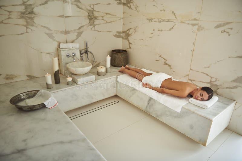 Giovane signora di calma che chiude i suoi occhi mentre rilassandosi nel bagno turco fotografia stock