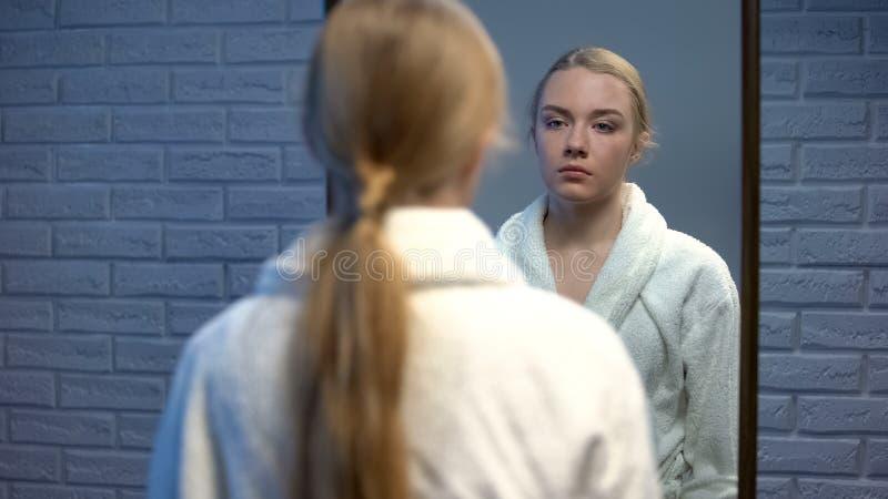 Giovane signora infelice nello sforzo che guarda in specchio, dolore di sofferenza dell'accappatoio di anima fotografia stock