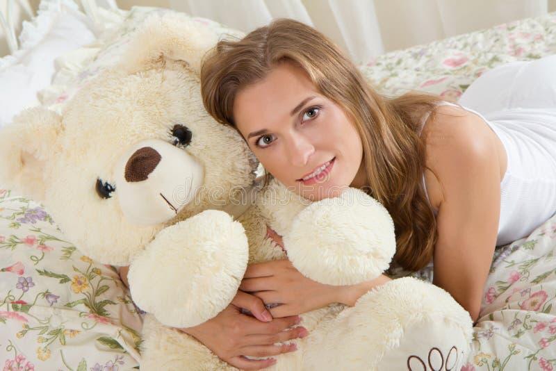 Giovane signora a letto con l'orsacchiotto fotografie stock