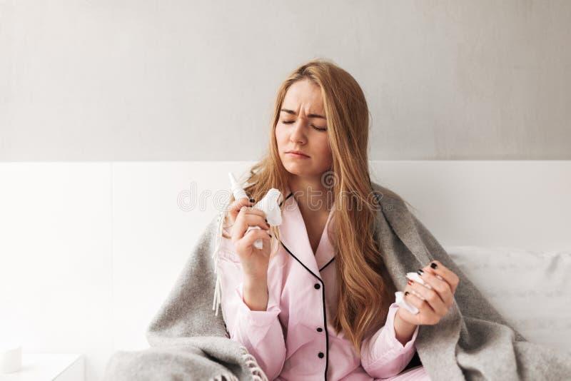 Giovane signora malata che si siede con il plaid sul letto a casa immagini stock libere da diritti