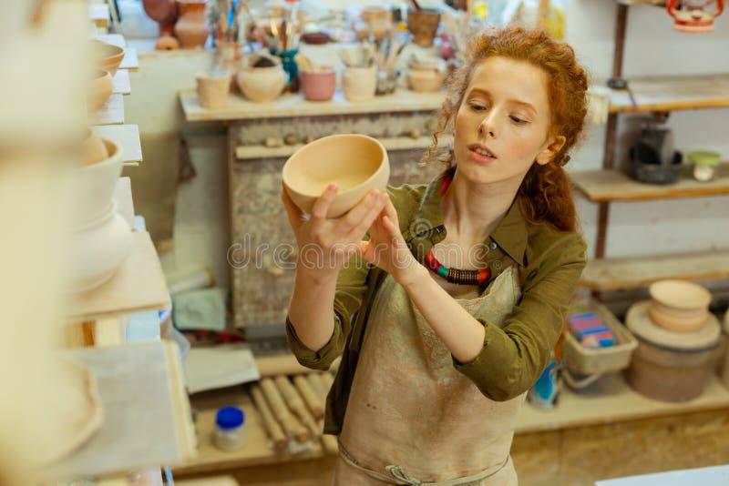 Giovane signora messa a fuoco in grembiule protettivo osservando vaso finito fotografia stock