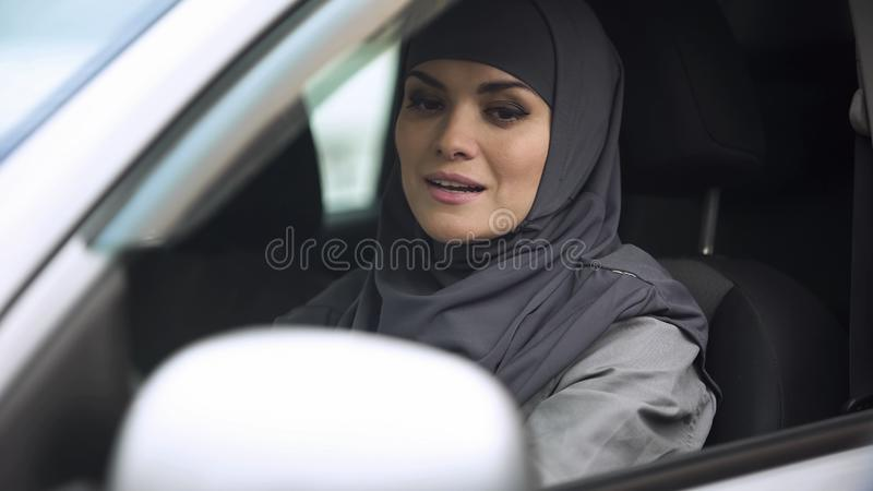 Giovane signora musulmana che guarda in specchietto retrovisore che si siede in automobile, preparante guidare fotografia stock