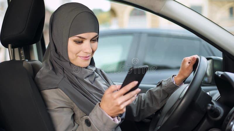 Giovane signora musulmana che si siede in automobile, facendo scorrere app sul telefono, cercante migliore itinerario fotografia stock