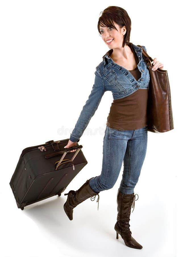 Giovane signora sorridente che tira i suoi bagagli immagine stock libera da diritti
