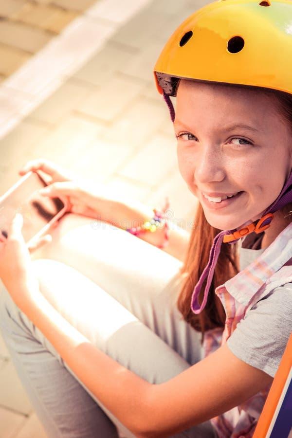 Giovane signora sveglia allegra in casco giallo che si intrattiene con il app dello smartphone immagine stock