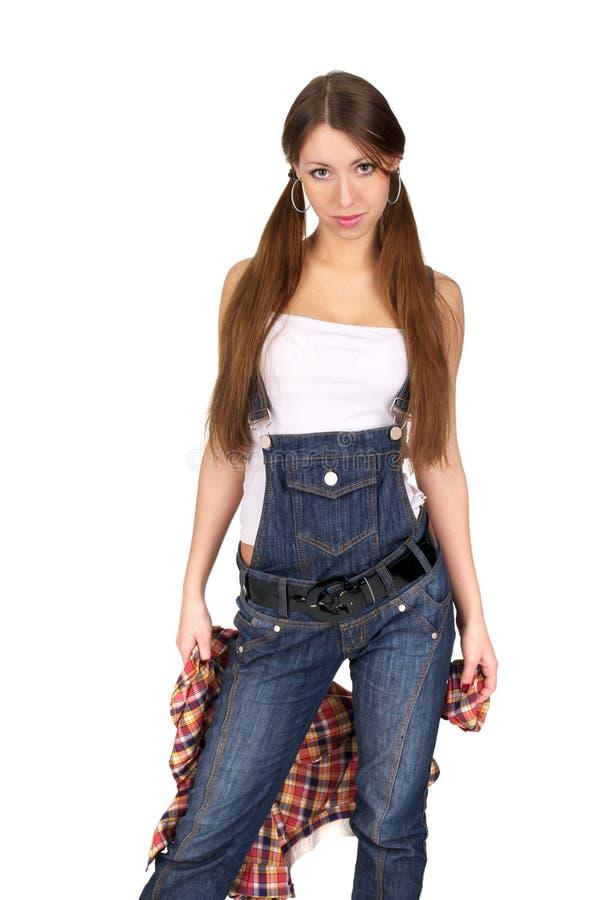 Giovane signora sveglia in jeans complessivi immagini stock