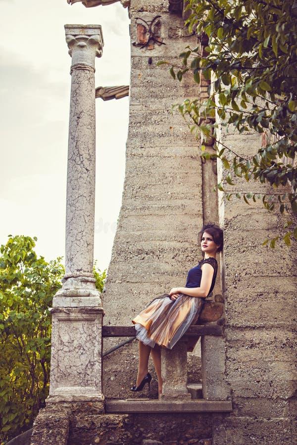 Giovane signora in vestito d'annata con il velo vicino alla colonna fotografia stock libera da diritti