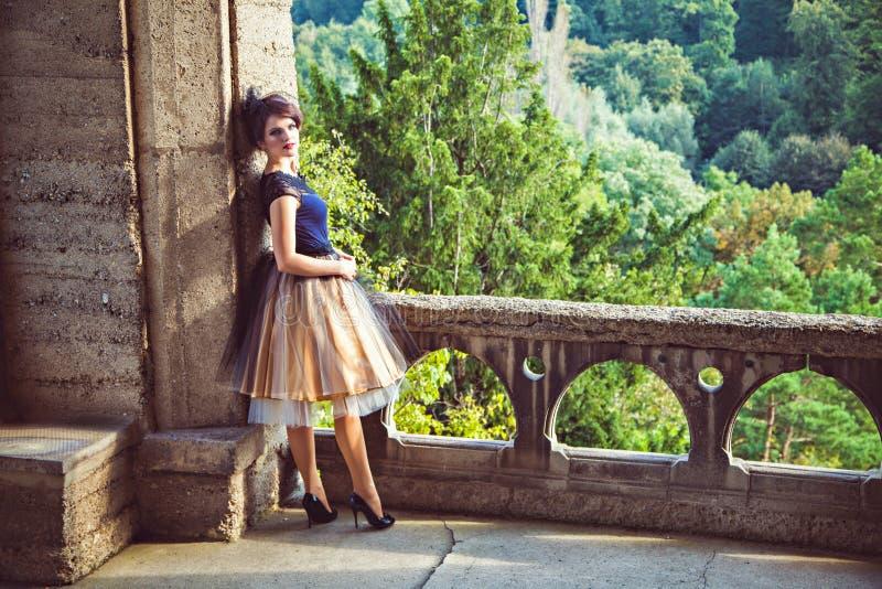 Giovane signora in vestito d'annata sul terrazzo del castello fotografia stock libera da diritti