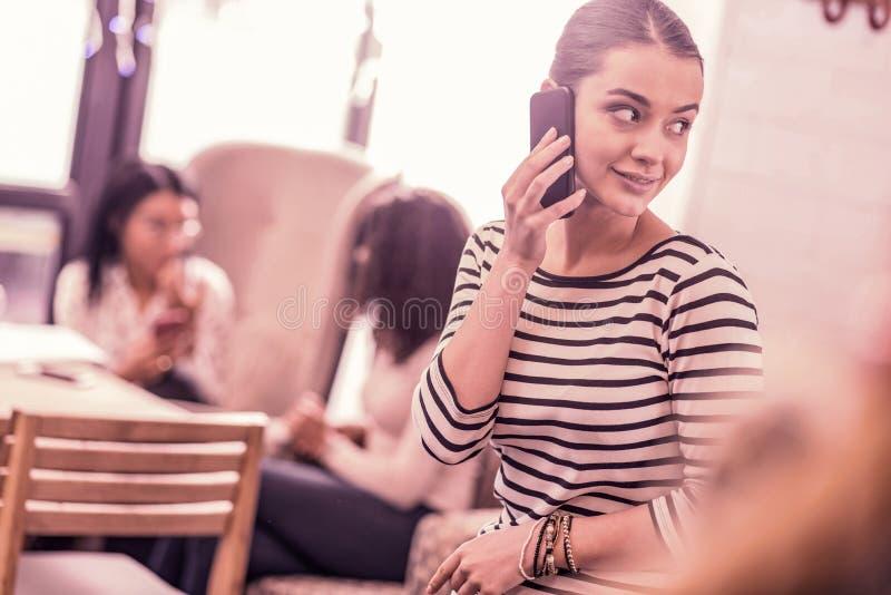 Giovane smartphone alla moda piacevole della tenuta della donna mentre chiamando il suo marito immagine stock libera da diritti