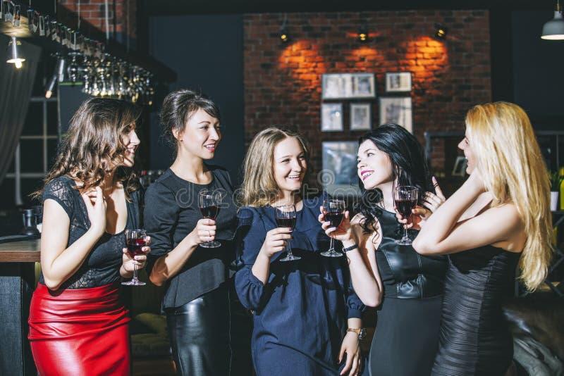 Giovane società allegra degli amici nella barra del club divertendosi spirito fotografia stock