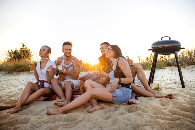 Giovane società degli amici che si rallegrano, riposante alla spiaggia durante l'alba fotografia stock