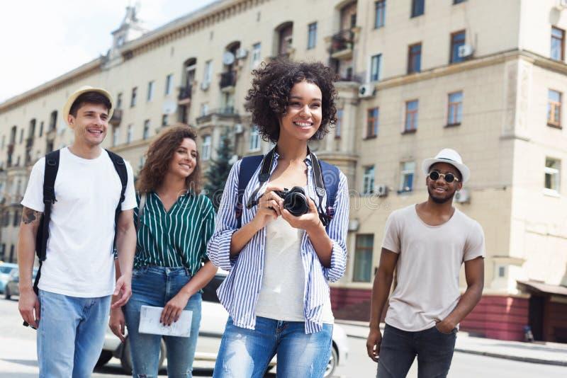 Giovane società dei pantaloni a vita bassa che cammina e che prende le immagini fotografia stock