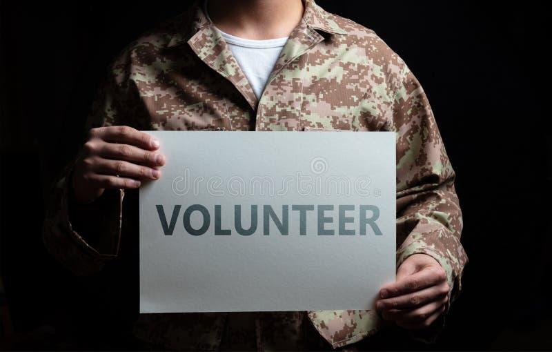 Giovane soldato che tiene una carta, condizione volontaria del testo sul fondo nero immagini stock