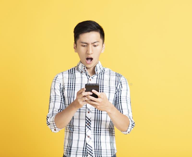 Giovane sorpreso facendo uso dello Smart Phone fotografia stock libera da diritti