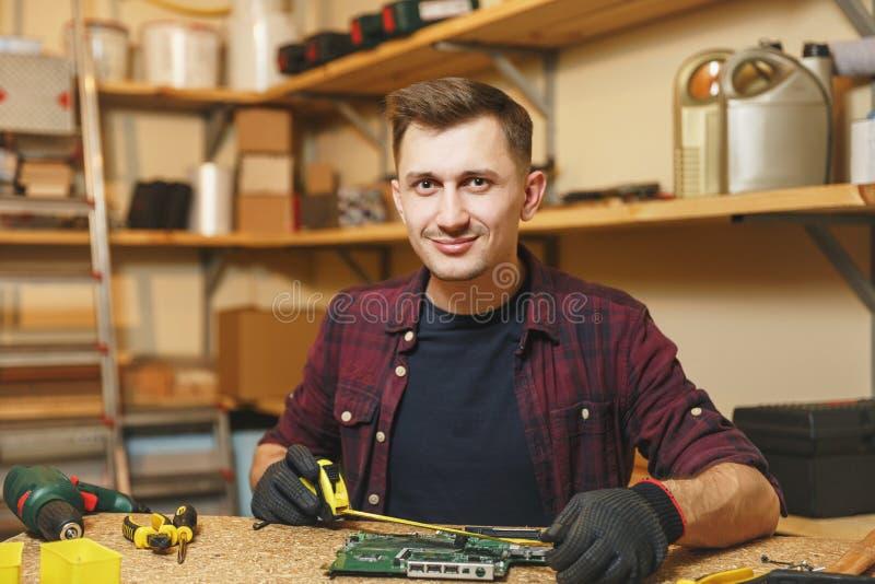 Giovane sorridente bello che lavora nell'officina di carpenteria al posto di legno della tavola con il pezzo di legno immagine stock