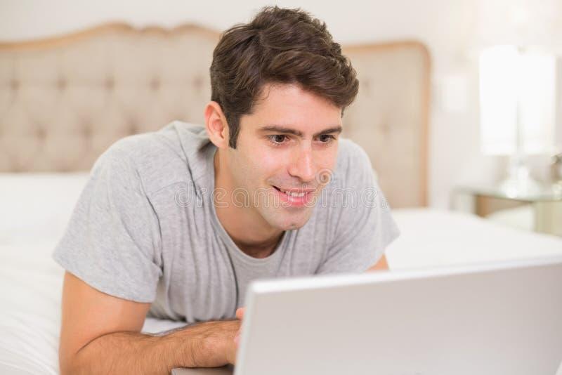 Giovane sorridente casuale che per mezzo del computer portatile a letto immagini stock